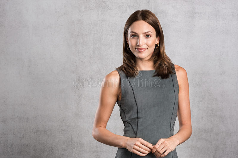 Young confident businesswoman. Young business woman feeling confident standing against grey wall with copy space. Portrait of beautiful smiling woman in formal stock image