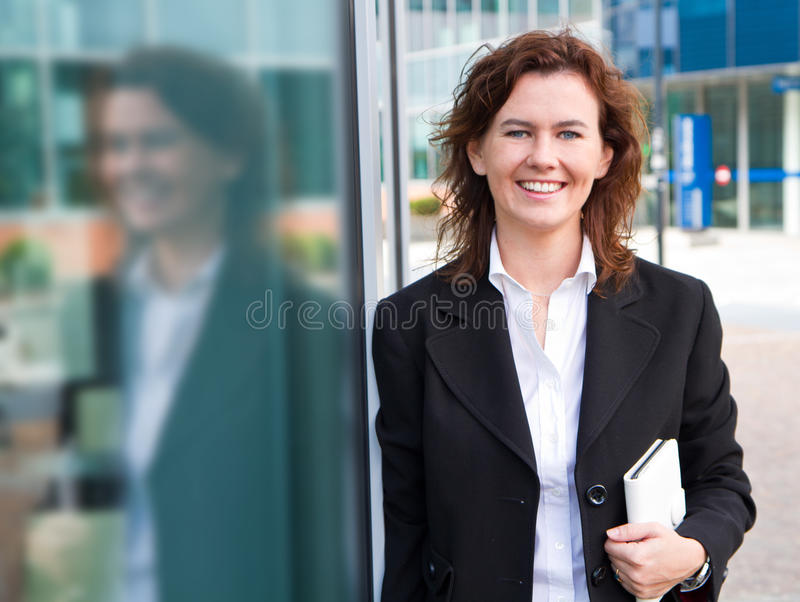 Young confident businesswoman with folder near the office build stock image