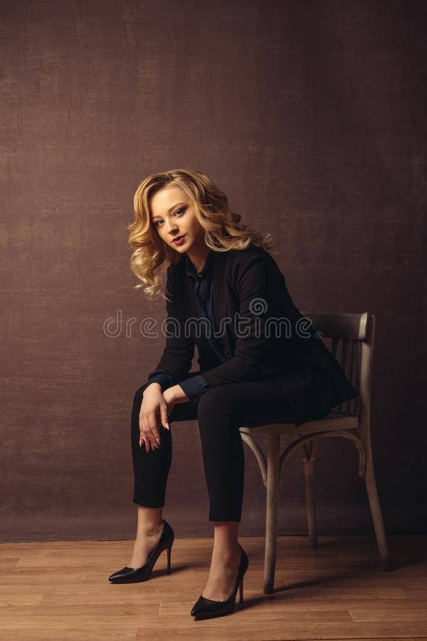 Young confident businesswoman sitting on the chair on gray background stock photo