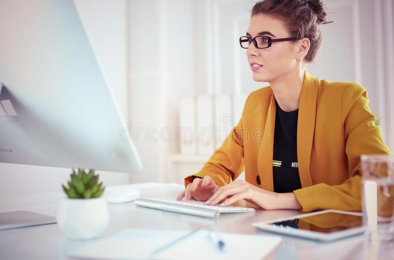 Young confident businesswoman working at office desk and typing with a laptop.  stock photography