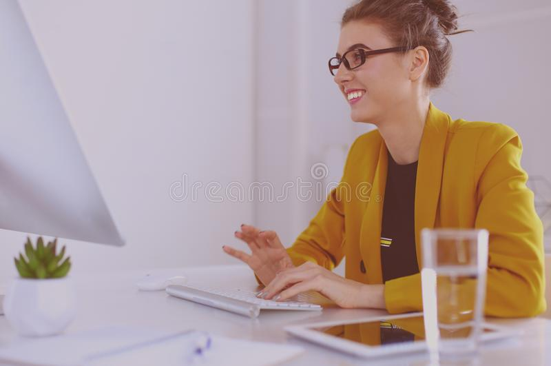 Young confident businesswoman working at office desk and typing with a laptop.  stock images