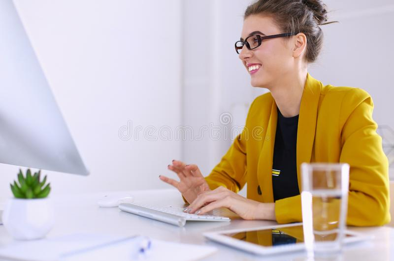 Young confident businesswoman working at office desk and typing with a laptop.  royalty free stock photography