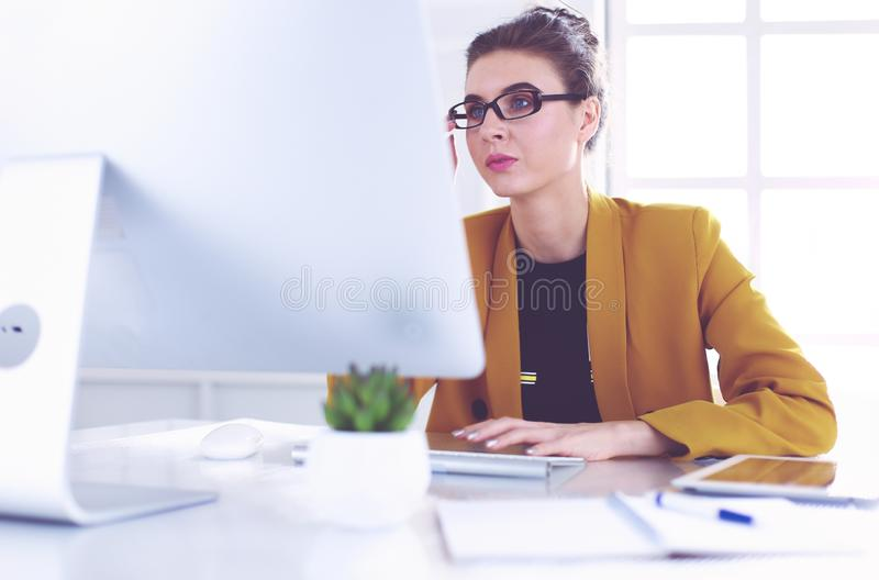 Young confident businesswoman working at office desk and typing with a laptop.  royalty free stock photo