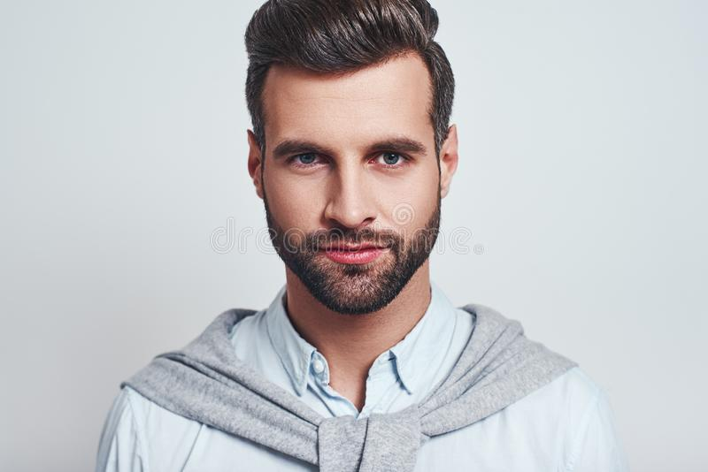 Young and confident. Close up portrait of a handsome bearded man looking at camera and smiling stock image