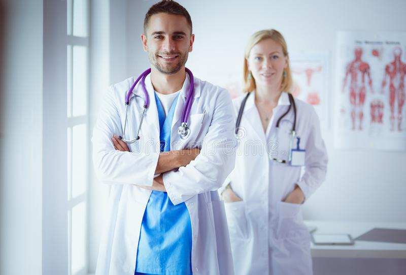 Young and confident doctors portrait standing in medical office stock photography