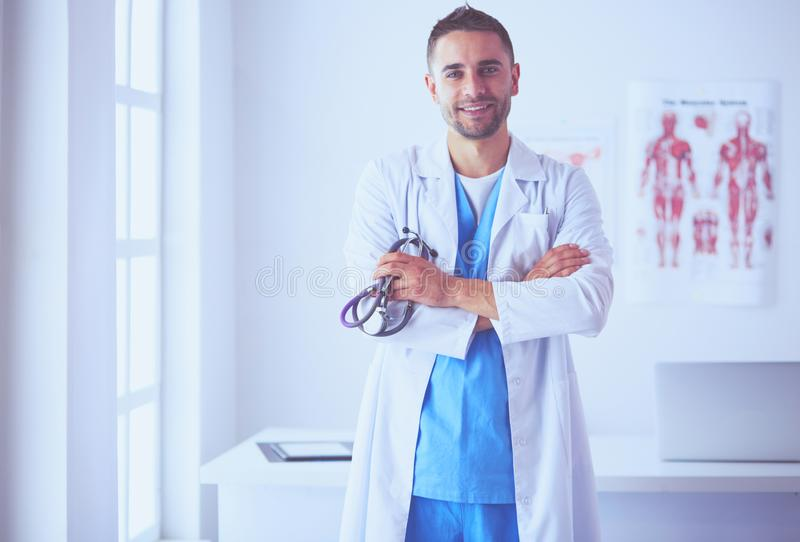 Young and confident male doctor portrait standing in medical off royalty free stock images