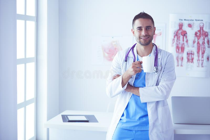 Young and confident male doctor portrait standing in medical office. stock photo