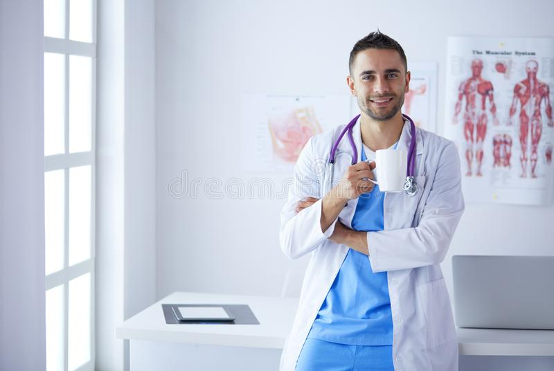 Young and confident male doctor portrait standing in medical office. stock images