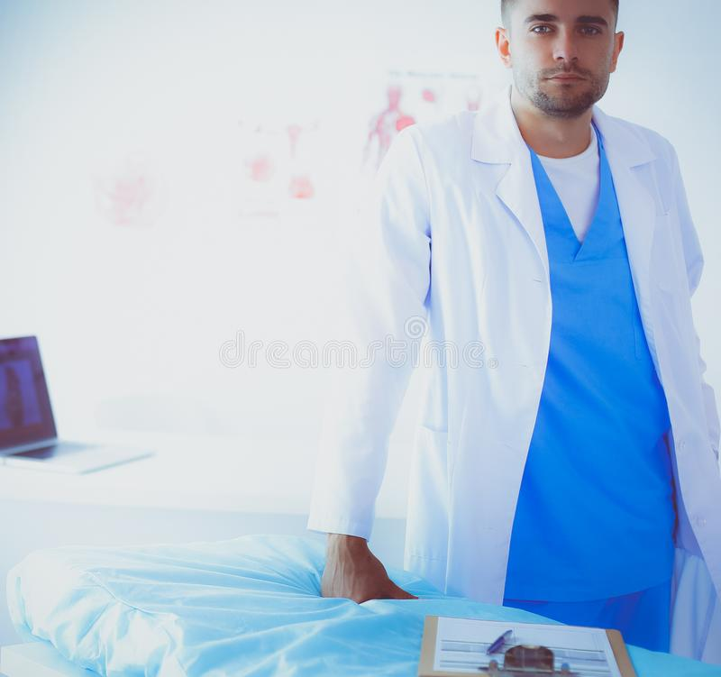Young and confident male doctor portrait standing in medical office royalty free stock photography