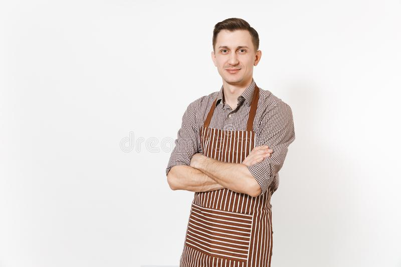 Young confident man chef or waiter holding hands crossed in striped brown apron, shirt isolated on white background royalty free stock photo