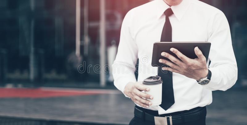 Young confident man economist holding digital tablet reading email or looking stock marketing with morning time. royalty free stock image