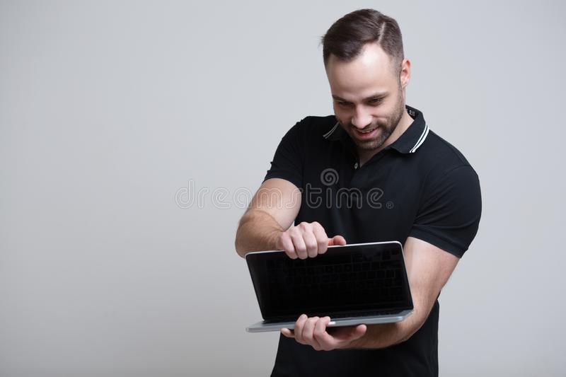 Young confident man opening laptop over white background stock photography