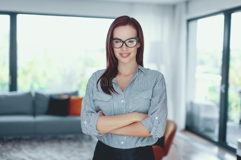 Young confident modern businesswoman posing in living room royalty free stock photography
