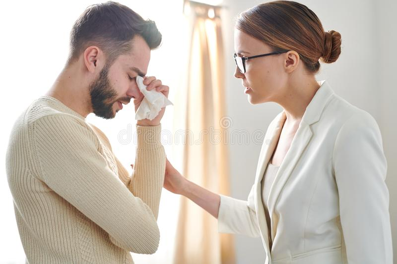 Supportive counselor. Young confident psychiatrist standing in front of her crying patient while comforting him stock image