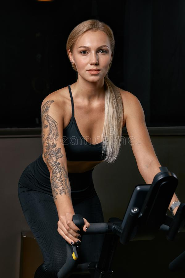 Young confident woman athlete exercising on bicycle indoors. Attractive determined fitness girl doing cycling exercises royalty free stock images