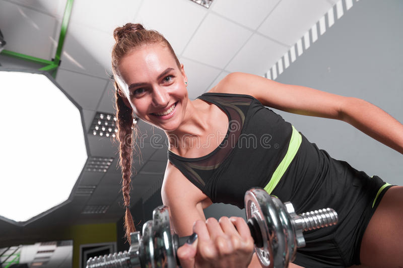 Young confident woman doing biceps curl exercise with dumbbells in fitness center. Slim girl training in the gym. With dumbbells royalty free stock photos