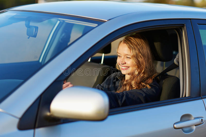 Young confident woman driving a car. Beautiful young confident woman driving a car royalty free stock photo