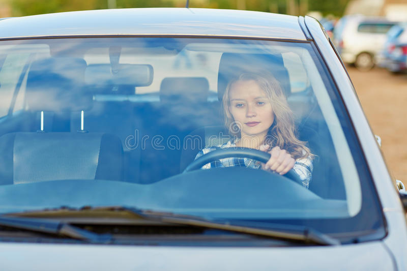 Young confident woman driving a car. Beautiful young confident woman driving a car royalty free stock images