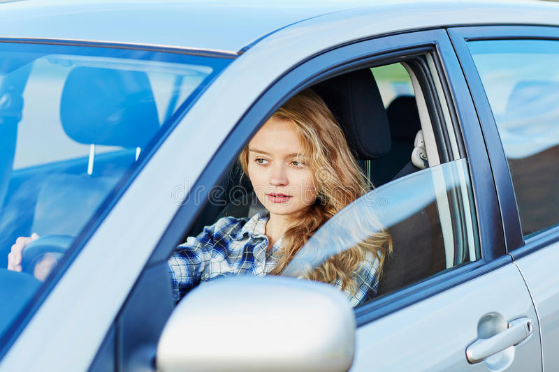 Young confident woman driving a car. Beautiful young confident woman driving a car stock photography