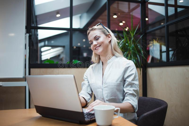 Young confident woman working on a laptop in the office. stock photos