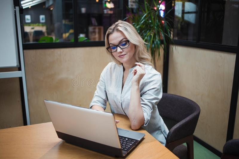 Young confident woman working on a laptop in the office. stock photography