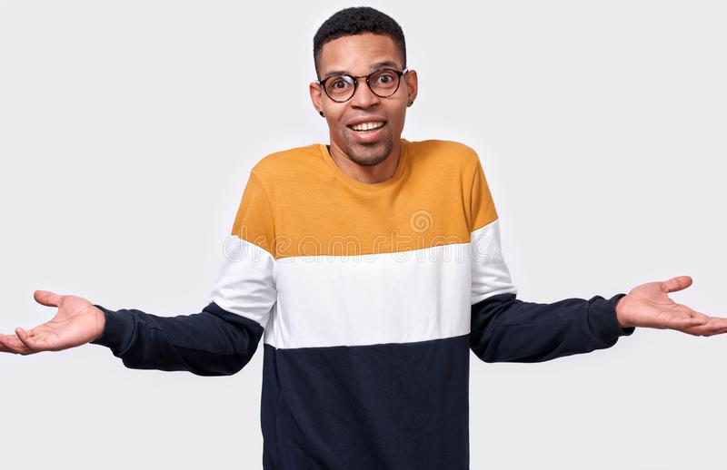 Young confused African American man shrugging with hands raised near shoulders smiling with sorry look as unaware or clueless. stock photo