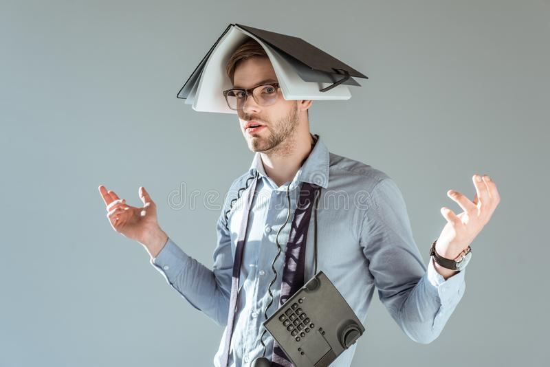 Young confused businessman holds notebook on his head and phone on neck stock photos