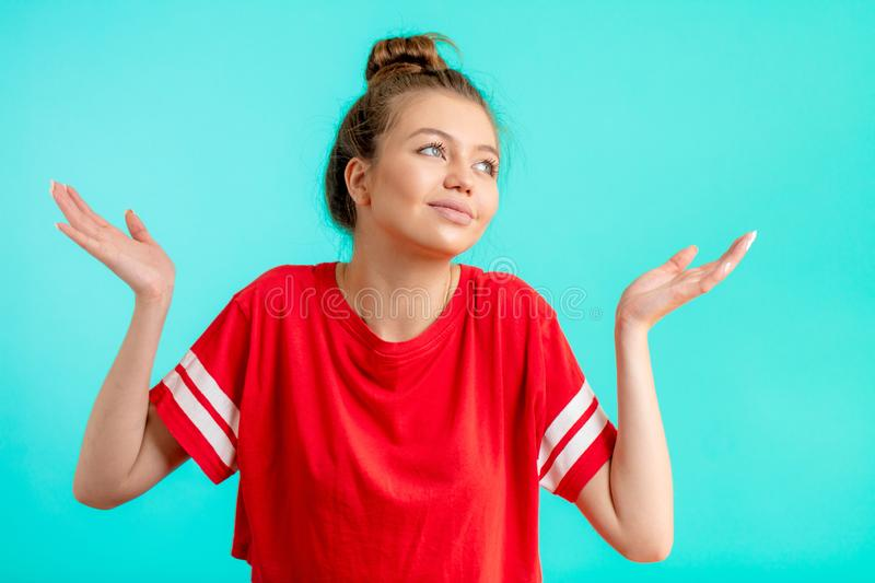 Young confused woman in fashion red t-shirt with arms out shrugs shoulders stock photos