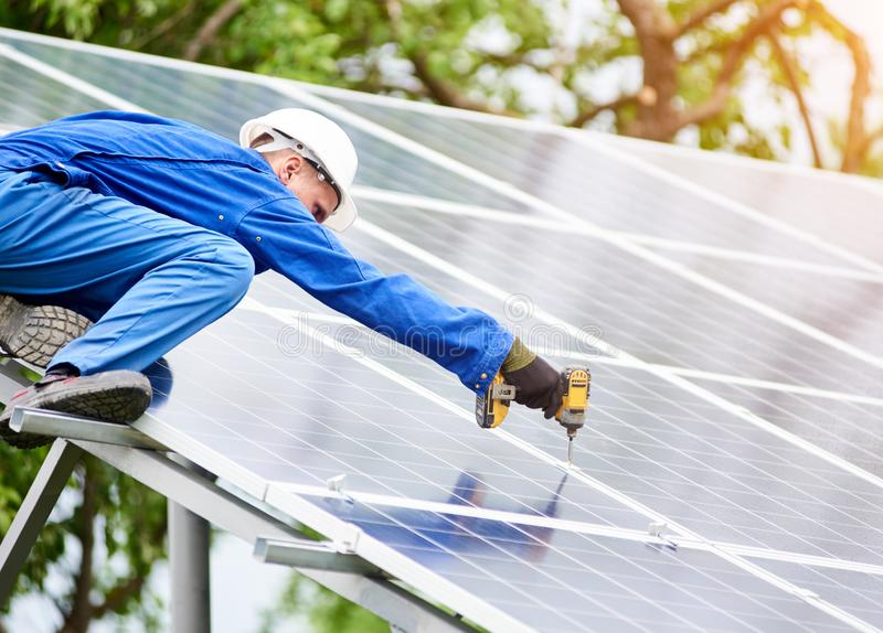 Installing of solar photo voltaic panel system. Young construction worker connects photo voltaic panel to solar system using screwdriver on sunny day royalty free stock photo