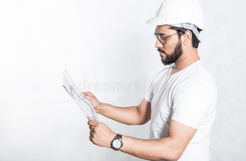 A young construction worker with glasses and a white protective helmet examines a drawing of a building. stock photo