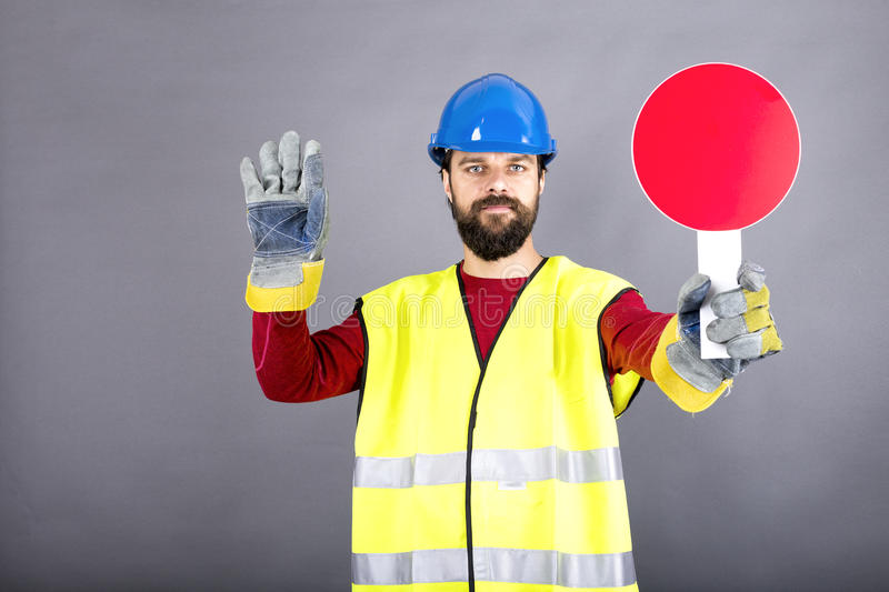 Young construction worker with hardhat stopping traffic royalty free stock photo
