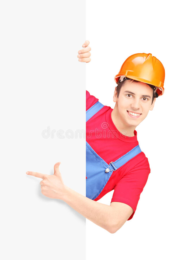 Download Young Construction Worker With Helmet Gesturing On A Blank Panel Royalty Free Stock Photo - Image: 31147255