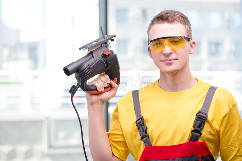 The young construction worker in yellow coveralls royalty free stock photography