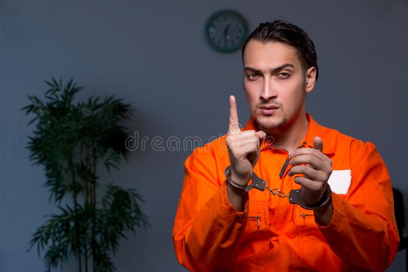 Young convict man sitting in dark room. The young convict man sitting in dark room stock photos
