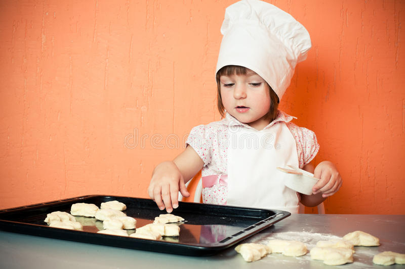 Young cook. In hat makes biscuits royalty free stock photography