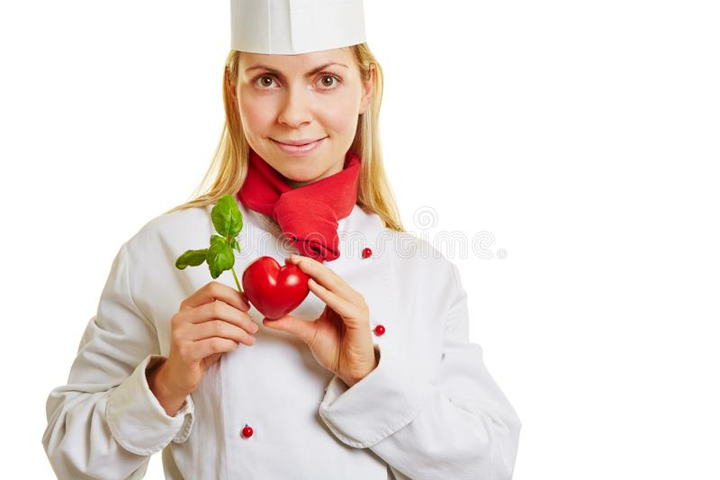 Young cook holds heart and basil royalty free stock photos