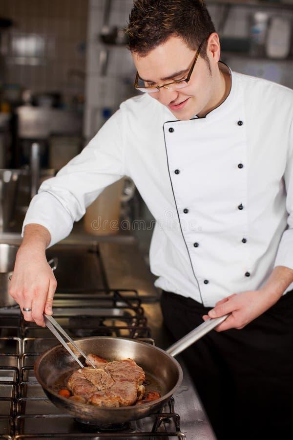 Young cook preparing steak in a pan. Smiling young cook preparing steak in a pan stock photos