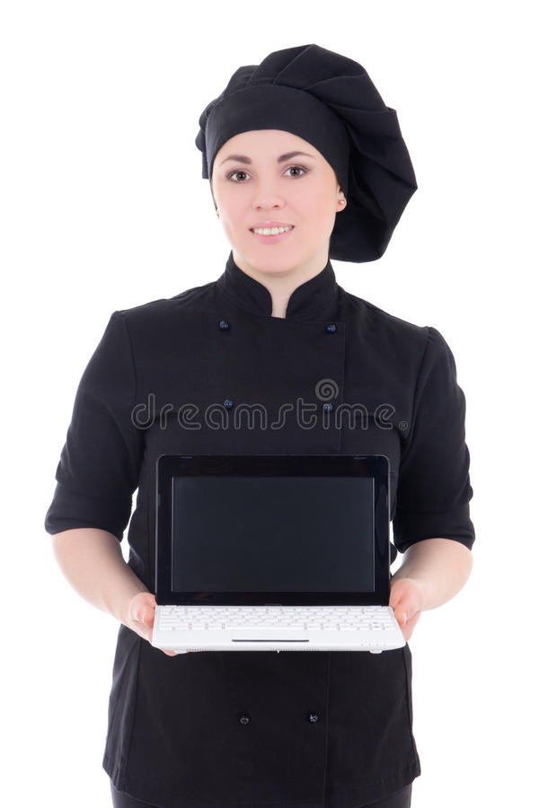 Young cook woman in black uniform showing laptop with copypaste. Isolated on white background stock photos