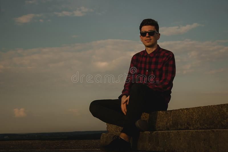 A young cool guy in hipsters shirt and sunglasses on the roof with blue sky and clouds royalty free stock photography