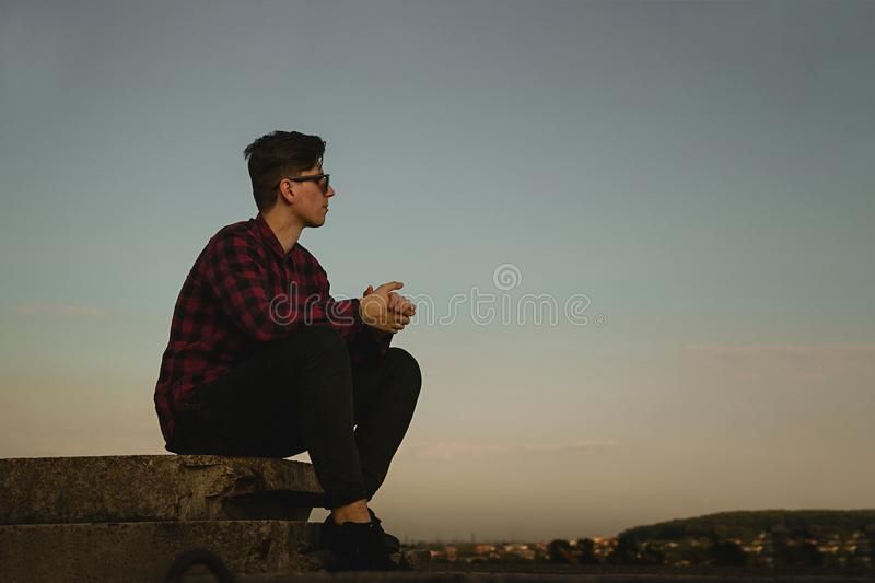 A young cool guy in hipsters shirt and sunglasses on the roof with blue sky and clouds royalty free stock photo