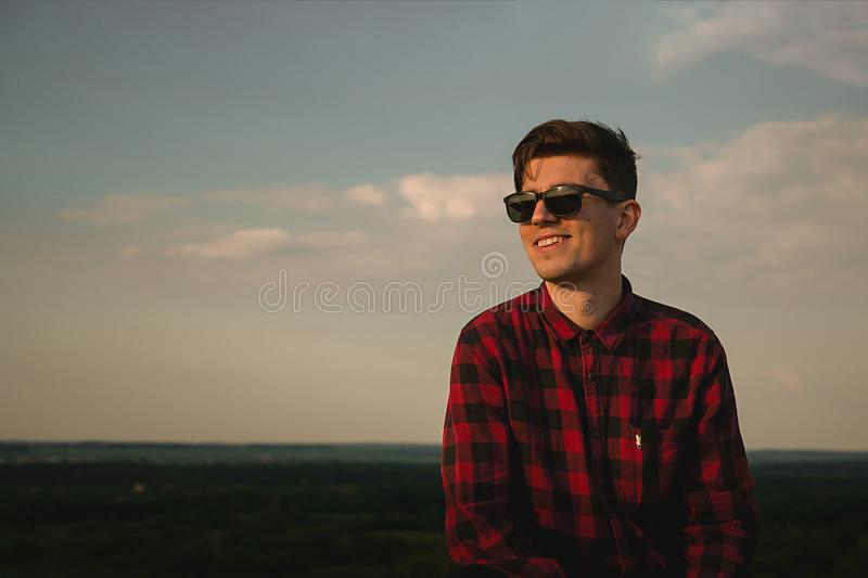 A young cool guy in hipsters shirt and sunglasses smiling on the roof with blue sky and clouds stock photos