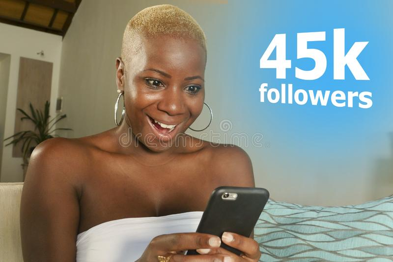 Young cool and happy black African American woman relaxed at home using internet mobile phone smiling cheerful networking getting stock image