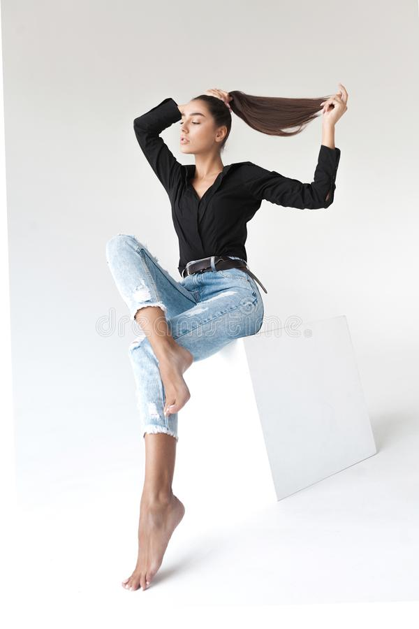 Young cool hipster girl posing in black shirt and blue banana jeans on white background stock image
