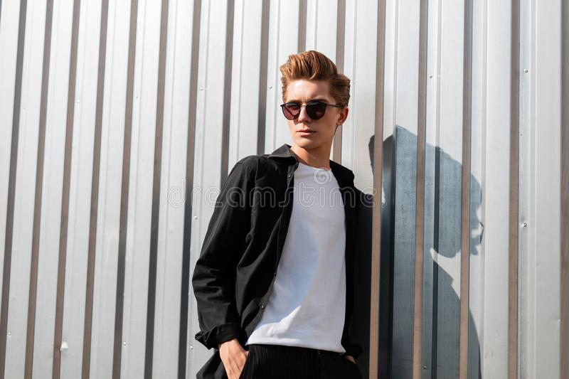 Young cool hipster man with a trendy hairstyle in elegant clothes in fashionable dark sunglasses poses near a silver metal wall. In the street on a sunny summer royalty free stock photography
