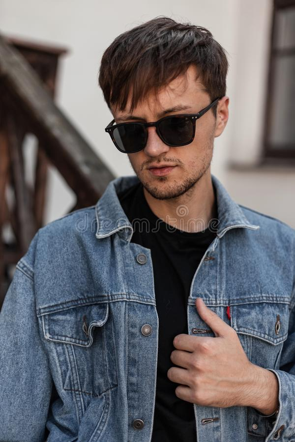 Young cool man straightens denim fashionable blue jacket. Attractive urban guy hipster in trendy sunglasses. In stylish spring clothes posing in the city near a royalty free stock photo