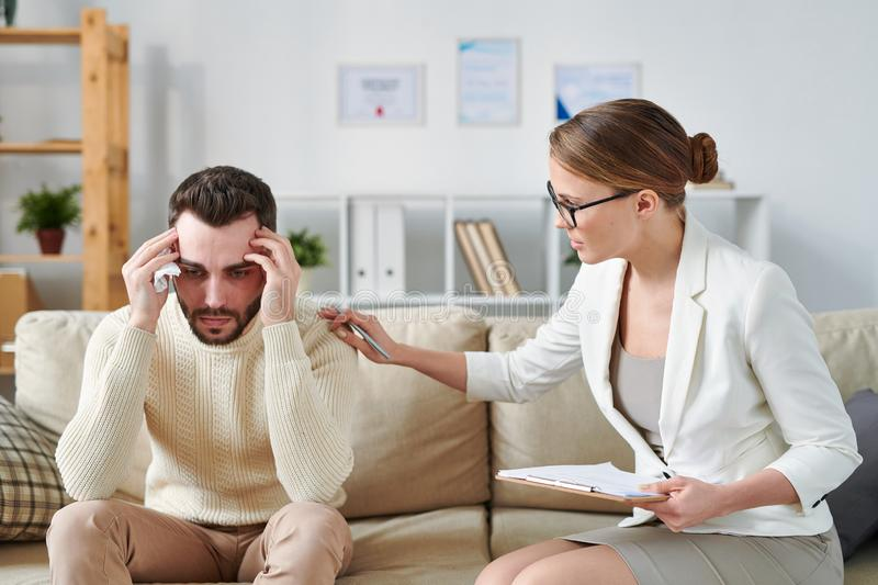 Reassuring patient. Young counselor sitting on couch next to stressed patient and reassuring him during individual session royalty free stock photo