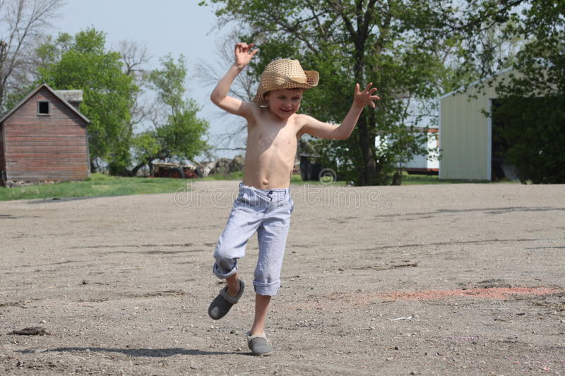 Young country boy jumps and plays on farm stock photo