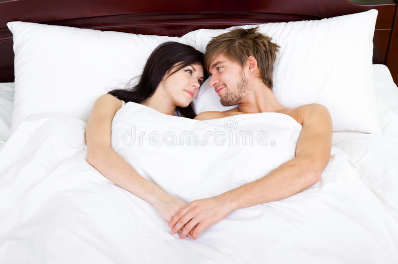 Young couple. Young lovely couple lying in a bed, happy smile stock image