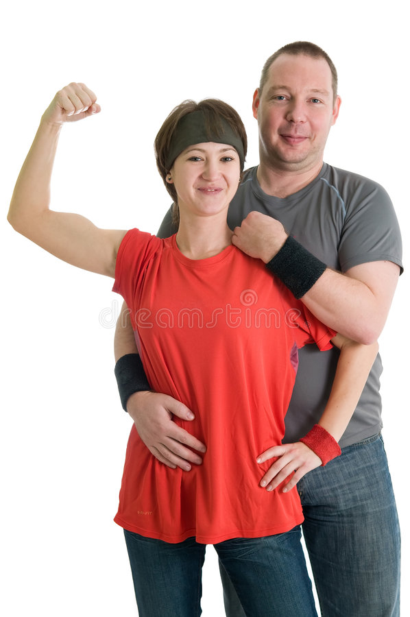 Young couple. Girl is showing her biceps in front of her partner. Isolated over white royalty free stock images