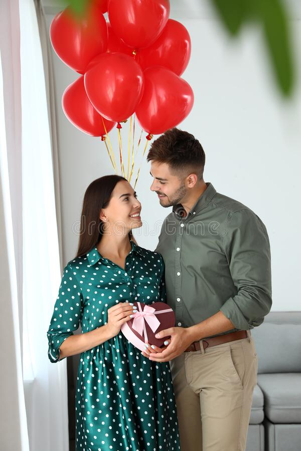 Young couple with air balloons and gift box. Celebration of Saint Valentine`s Day. Young couple with air balloons and gift box at home. Celebration of Saint royalty free stock images
